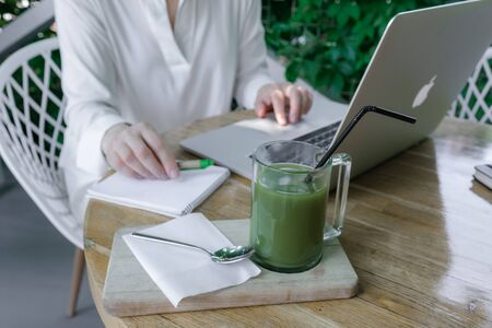 Glass Cup of Green Matcha late Coffee or Tea stay on the table near Workplace of Freelancer or Blogger. Halthy and Fashion Drink. 版權商用圖片