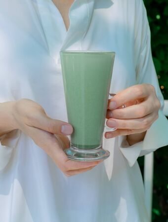 Female hands hold glass cup of green matcha late coffee or tea. Concept of halthy and fashion drink.