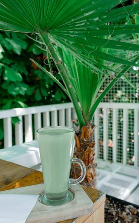 Cup of Green Matcha latte Coffee or Tea on Tropical Nature background with Palm Leaves.
