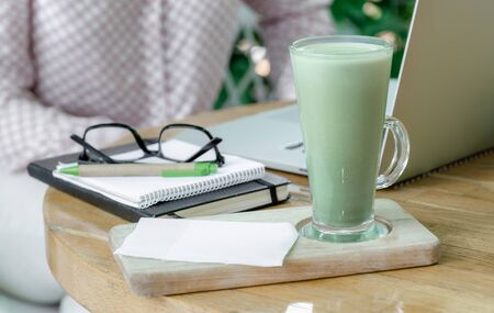 Glass Cup of Green Matcha latte Coffee or Tea stay on the table near Workplace of Freelancer or Blogger. Healthy and Fashion Drink.