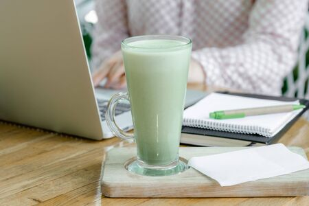 Glass Cup of Green Matcha latte Coffee or Tea stay on the table near Workplace of Freelancer or Blogger. Halthy and Fashion Drink. 版權商用圖片