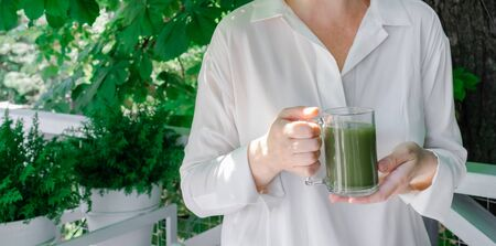 Female hands hold glass cup of green matcha late coffee or tea on the tropical background. Concept of healthy and fashion drink. 版權商用圖片