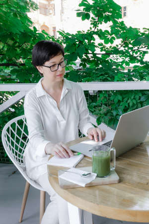 Glass Cup of Green Matcha late Coffee or Tea stay near Workplace of Freelancer or Blogger. Concept of Healthy Food in Menopause Period. 版權商用圖片