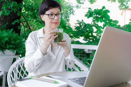 Middle Aged Woman hold glass cup of green Matcha Latte Coffee or Tea on the Tropical background. Concept of healthy food in menopause period. 版權商用圖片