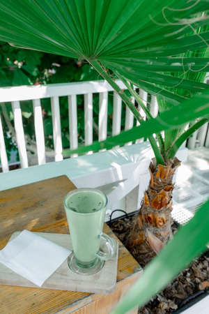 Cup of Green Matcha latte Coffee or Tea on Tropical Nature background with Palm Leaves. Concept of healthy food. 版權商用圖片