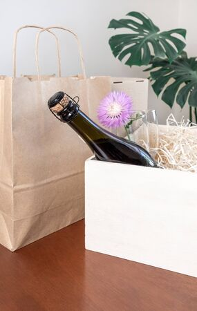 Wine Bottle and Glasses in white box with straw on the tropical leaves background. Concept of Delivery Service for Customer. 版權商用圖片