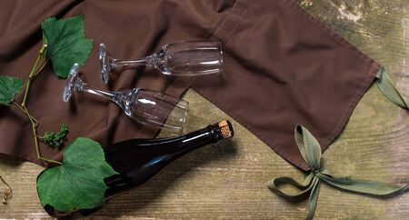 Wine Bottle and Glasses on the wooden background with brown apron. Concept of Delivery Service for Customer.