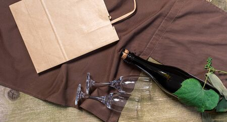 Wine Bottle, Glasses, packing bag and box on the wooden background with brown apron. Concept of Delivery Service for Customer.