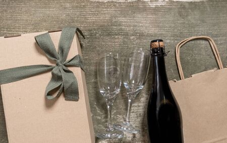 Wine Bottle, Glasses, Packing Bag and Box on the Wooden Background. Concept of Delivery Service for Customer. 版權商用圖片