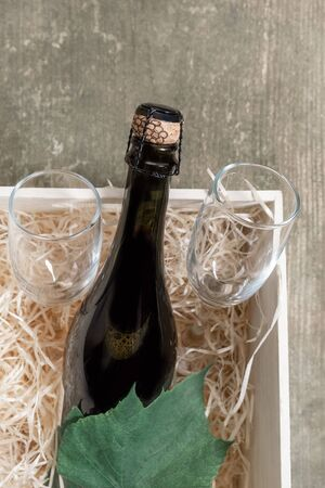 Wine Bottle and Glasses in white box with straw. Concept of Delivery Service for Customer.