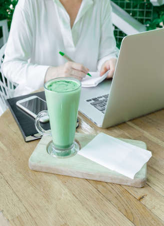 Workplace of Female Freelancer or Blogger outside in cafe or home tertace with cup of Matcha Tea. Concept of New Skills for Middle Aged People.