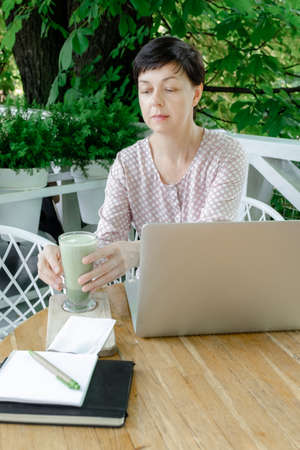 Woman Freelancer or Blogger sitting at the work place with Cup of Green Matcha late Coffee or Tea. Concept of Healthy Food in Menopause Period.