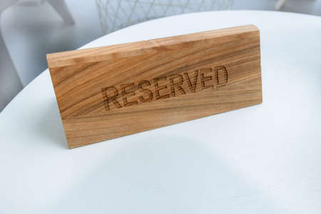 A tag of reservation placed on table. Reserved logo in a restaurant or summer terrace of cafe.