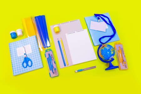 School supplies and stationery, desk, globe, pencils, pens, notebooks on the yellow table.