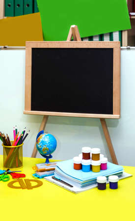 School supplies and stationery, desk, globe, pencils, pens, notebooks, black board on the yellow table. 版權商用圖片
