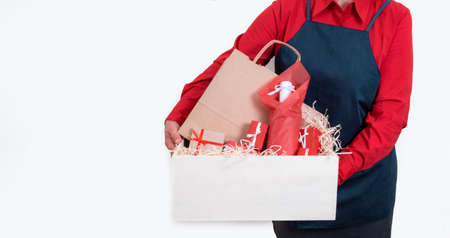 Hands of Deliver in red shirt and apron hold Gifts, Packing boxes and bottle of wine on the white background, delivery concept.