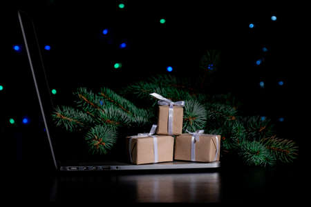 Laptop, Gift's Boxes and Christmas Tree on the black background with lights.