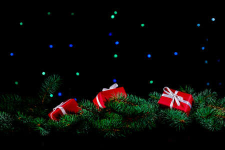 Red Gift's Boxes and Christmas Tree on the black background with lights.
