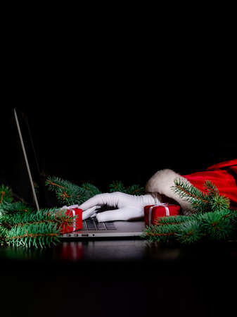 Hand of Santa Claus writes by laptop on the black background with lights.