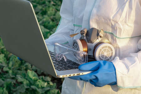An Agronomist dressed in a white protective suit, mask and blue gloves holds Laptop against the Field with Harvest. Problems of Chemical and Pesticides concept.