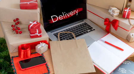 Laptop with gifts, Packing boxes and Shopping Bag on the work place, delivery concept.