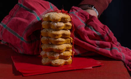 Hands shows Biscuits on Red Wooden table on the black background