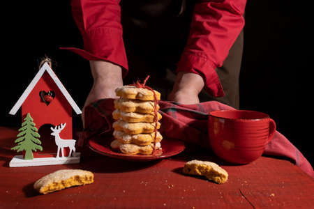 Hands shows Biscuits on Red Wooden table with Red Cup of coffee and New Year Toy