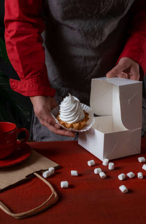 Confectioner holding white paper box with white cake near red table.