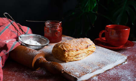 Fresh Puff staffed with plum or red currant jam on the table with a red cup and jar of jam on the black background.