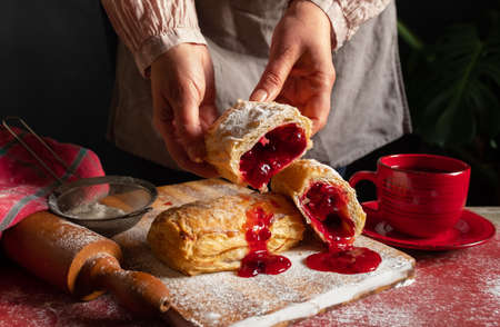 Female Hands bakes a Puff staffed with plum or red currant jam on the table.