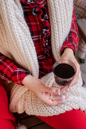 Woman holding glass of red wine dressed in red and white festive clothes. 版權商用圖片