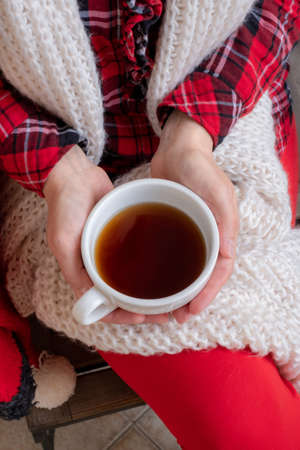 Woman's hands are holding white cup of tea or coffee dressed in red and white festive clothes.