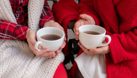 Women's hands are holding white cup of tea or coffee dressed in red and white festive clothes. 版權商用圖片