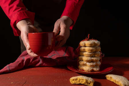 Hands, Set of Biscuits, Red Cup of Coffee or Tea on Red Wooden table on the black background.