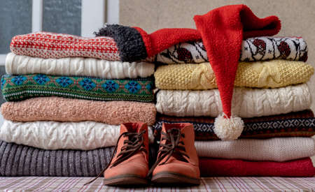 A Lot of Sweaters and Pullovers Different Colors folded in two Piles on the Table with old red shoes