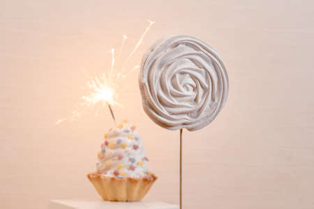 White Cakes with Sparklers on the Set Sail Champagne background. Banco de Imagens