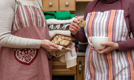 Women holding cup of Coffee and Biscuits dressed in festive aprons with a lot of different pullovers on the kitchen. Banco de Imagens