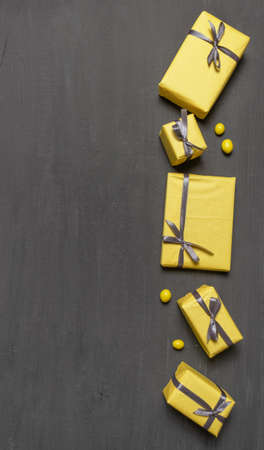 A Lot of Yellow Gift's Boxes on the Gray Wooden Background, top view. Banco de Imagens - 160709686