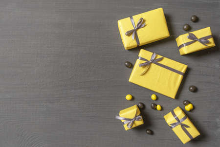 A Lot of Yellow Gift's Boxes on the Gray Wooden Background, top view. Banco de Imagens - 160709306