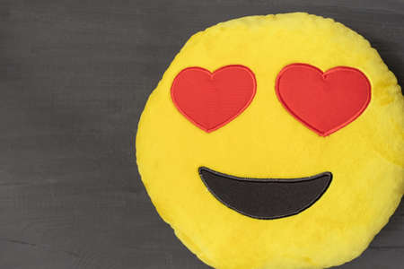 Yellow Pillow with two Red Hearts and Smile on the Gray background us a Gift in the Valentine's Day, top view. Banco de Imagens