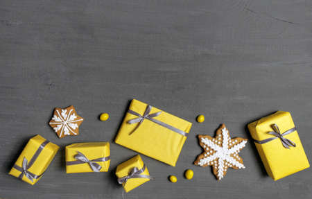 A Lot of Yellow Gift's Boxes on the Gray Wooden Background, top view.