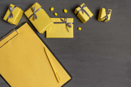 A Lot of Yellow Gifts Box and resume sheet on the Gray Color Background, top view.