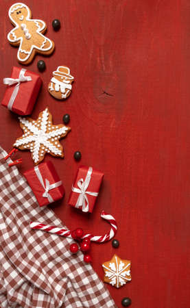 Set Festive New Year Biscuits, Gifts and Snowflake on Red Wooden Background Banco de Imagens