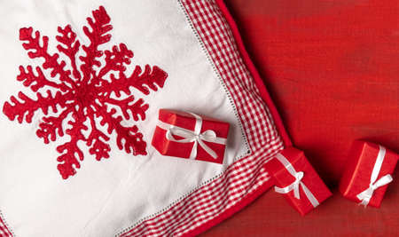 White Pillow with Red Snowflake and red Gifts Boxes on the Red Wooden Background