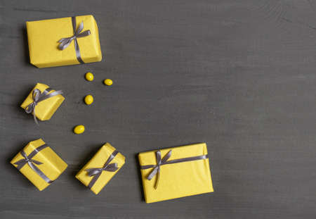 A Lot of Yellow Gift's Boxes on the Gray Wooden Background, top view. Banco de Imagens - 160709725
