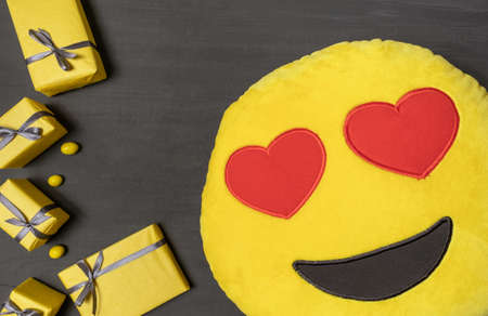 A Lot of Yellow Gift's Boxes and yellow Pillow with Red Hearts on the Gray Wooden Background, top view.