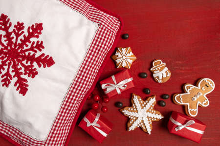 Set Festive New Year Biscuits, Gifts and Pillow with red Snowflake on Red Wooden Background Banco de Imagens