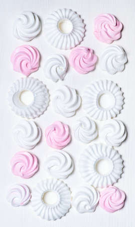 Set of white and pink marshmallow and meringue cookies on the white background, top view.
