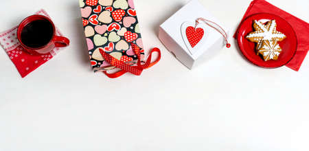 Shopping bag, white box, cup of coffee, biscuit and red Heart of Valentine's Day on white background Banco de Imagens