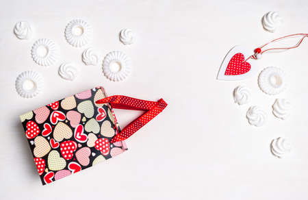 Shopping bag, Marshmallow or Meringue White cookies and red Heart of Valentine's Day on white background, delivery concept. Banco de Imagens